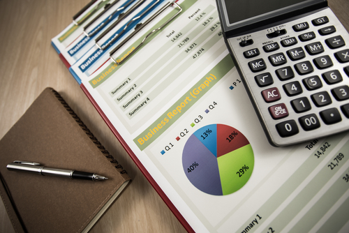 Printed business reports - showing graphs and figures - alongside a calculator, notebook and pen