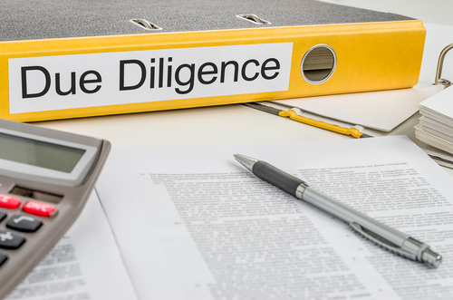 Yellow binder with Due Diligence label alongside calculator and pen