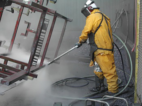 A worker using a Metco distributed Jetstream product to clean industrial equipment