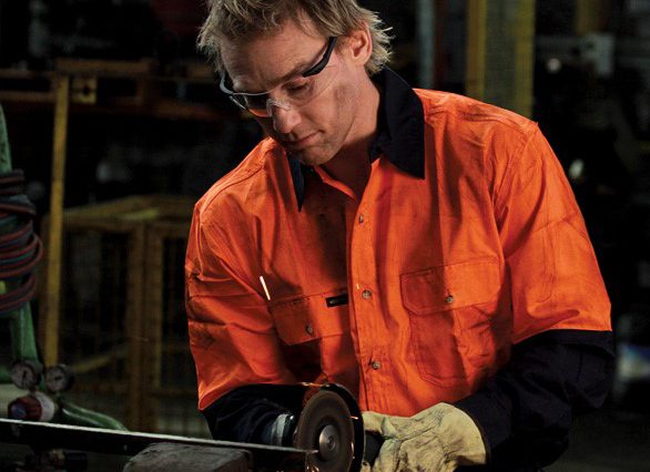 Model wearing workforce safety shirt, gloves, and goggles